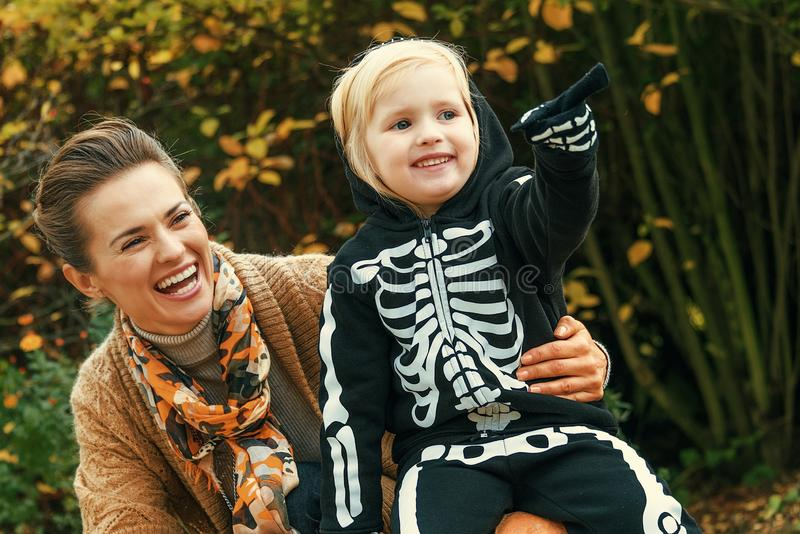 Mother and daughter on Halloween at park pointing at something stock image