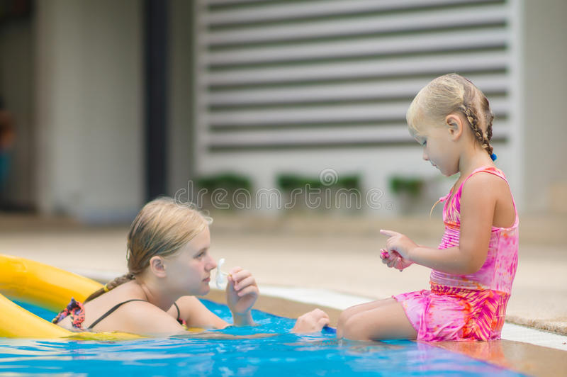 Mother and daughter have fun at pool side in tropical beach resort stock image