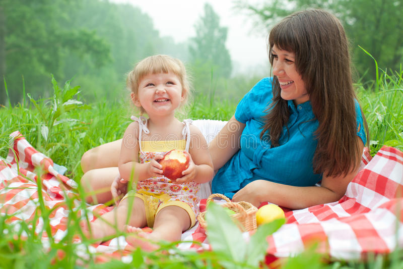 Mother And Daughter Have Picnic Eating Apples Stock Photo