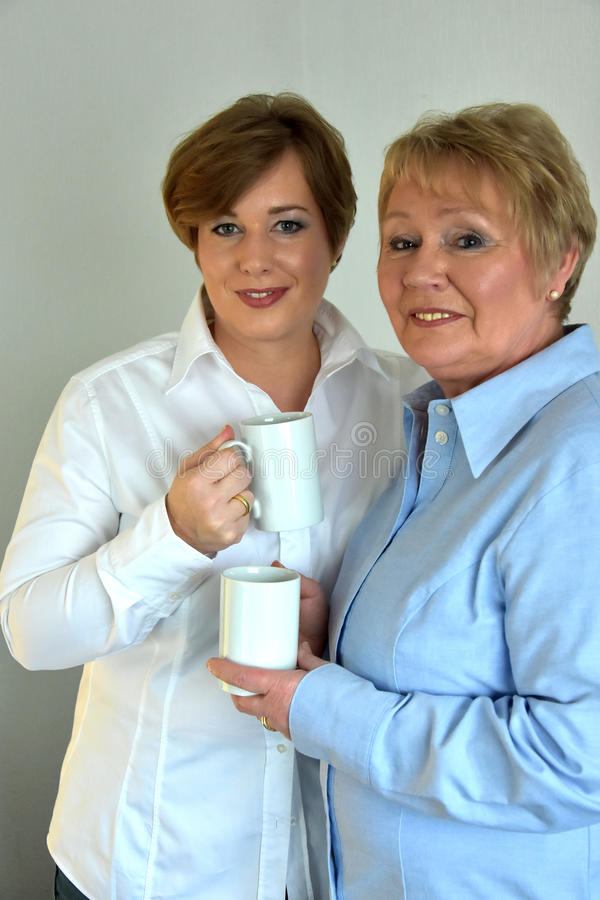 Mother and daughter. Having a cop of coffee stock photos