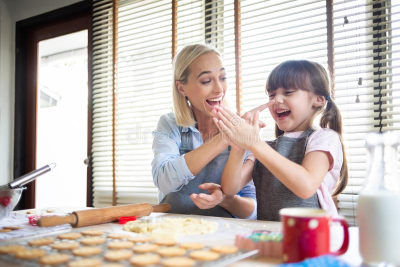 Mother and daughter having fun. Happy Mother and daughter having fun during preparing the dough, bake cookies in the kitchen royalty free stock photos