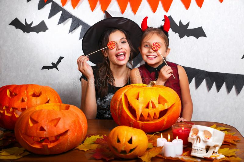 Funny Mother and daughter having fun at home. Happy family preparing for Halloween. People wearing carnival costumes. Mother and daughter having fun at home stock photography