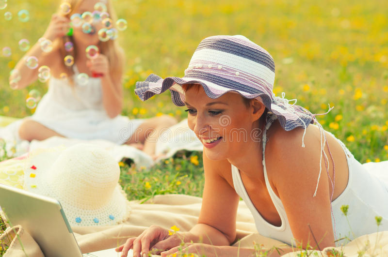 Mother and daughter having fun on meadow in spring stock photo