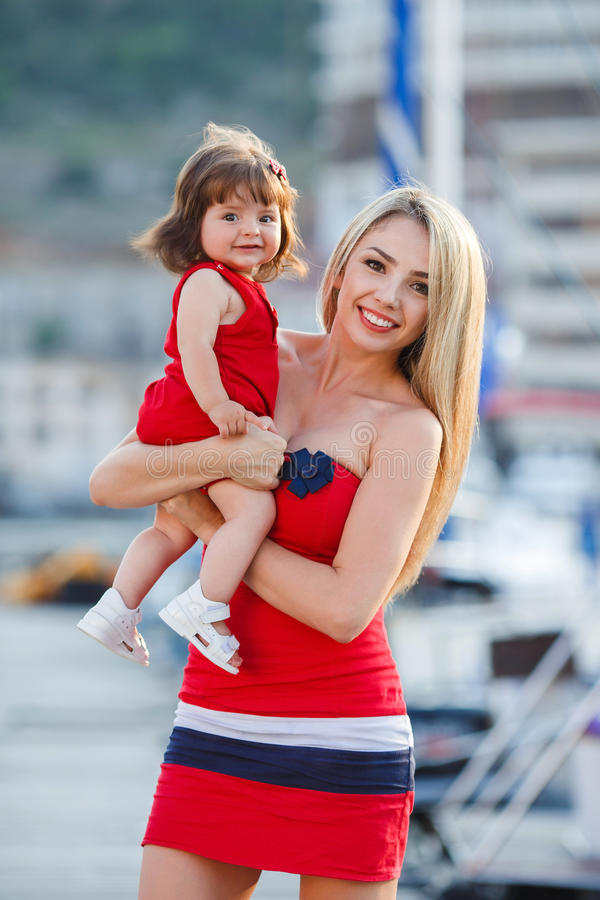 Mother and daughter having fun outside on the dock. A young mother,blond with long straight hair and her little daughter,a brunette with beautiful hair and brown royalty free stock image