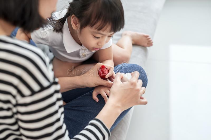 Mother and daughter having fun painting fingernails, family time concept royalty free stock photography