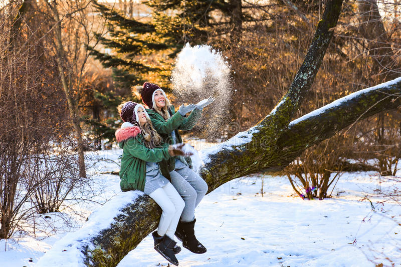 Mother and daughter having fun, playing, throwing snow and laughing in winter wood outdoor. royalty free stock photography