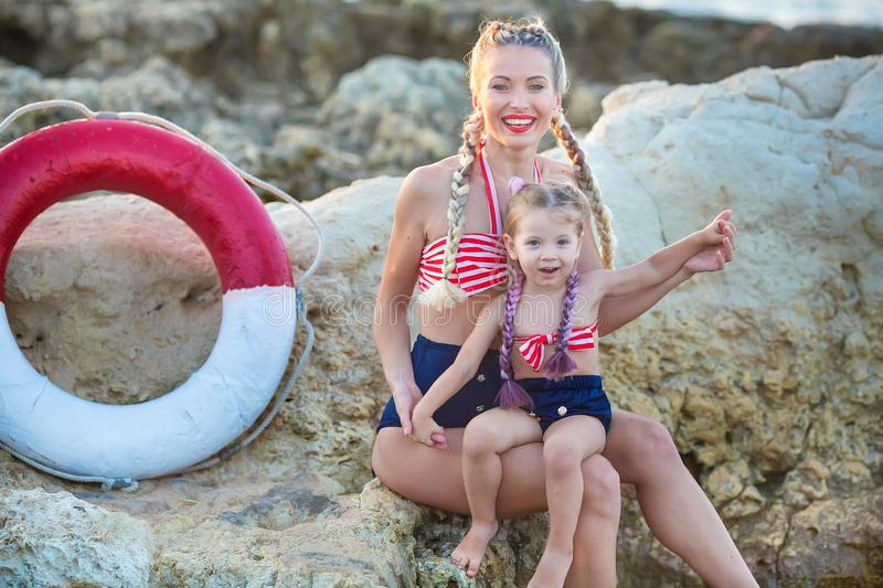Mother daughter having fun resting on the rocky beach. Two blond lady wearing retro swimming suits enjoy summer day together royalty free stock image