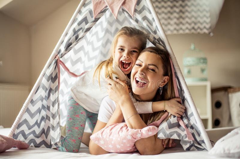 Mother and daughter having fun in teepee. Portrait stock photo