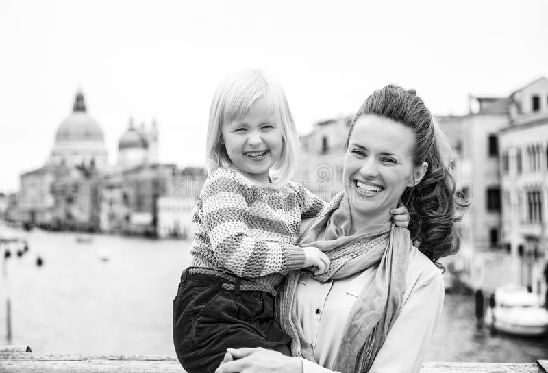 Smiling mother holding happy daughter in Venice on bridge stock photo
