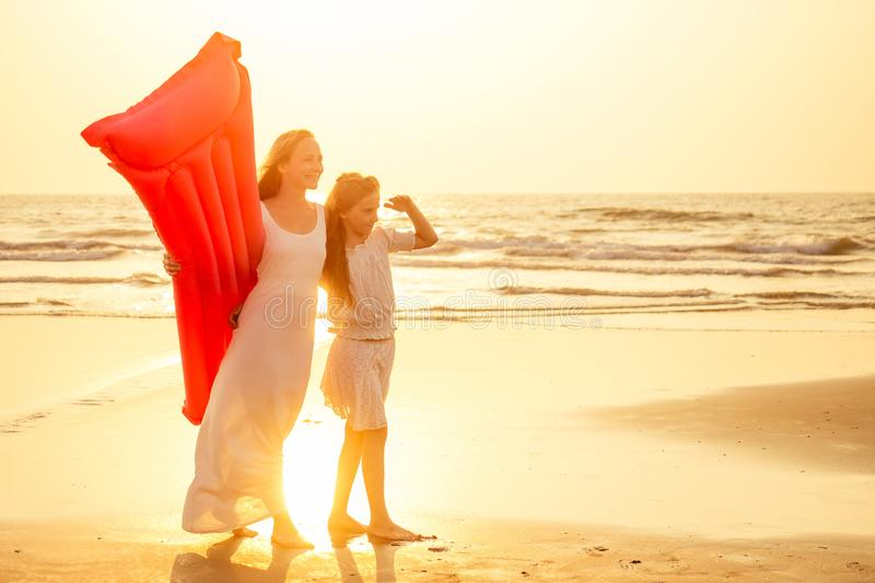 Mother and daughter having fun walking by summer sunset beach with air mattress in the sea clear blue water stock photo