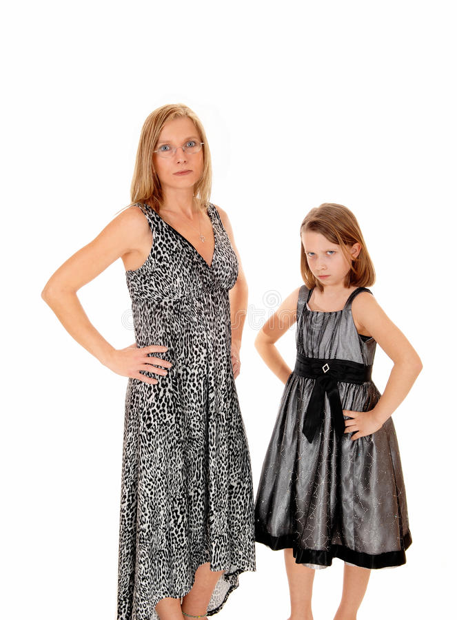 Mother and daughter having problem. A mom with her young daughter standing in dresses for white background having trouble with each other stock image