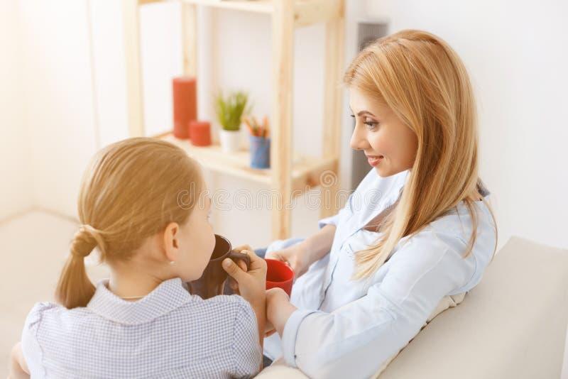 Mother and daughter having tea on sofa stock photos