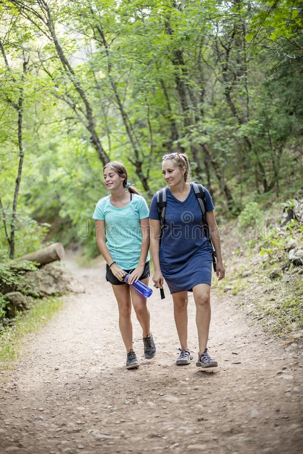 Mother and daughter hiking on a scenic mountain trail talking to each other. Mother and daughter hiking together along a scenic mountain trail on a summer day stock photography