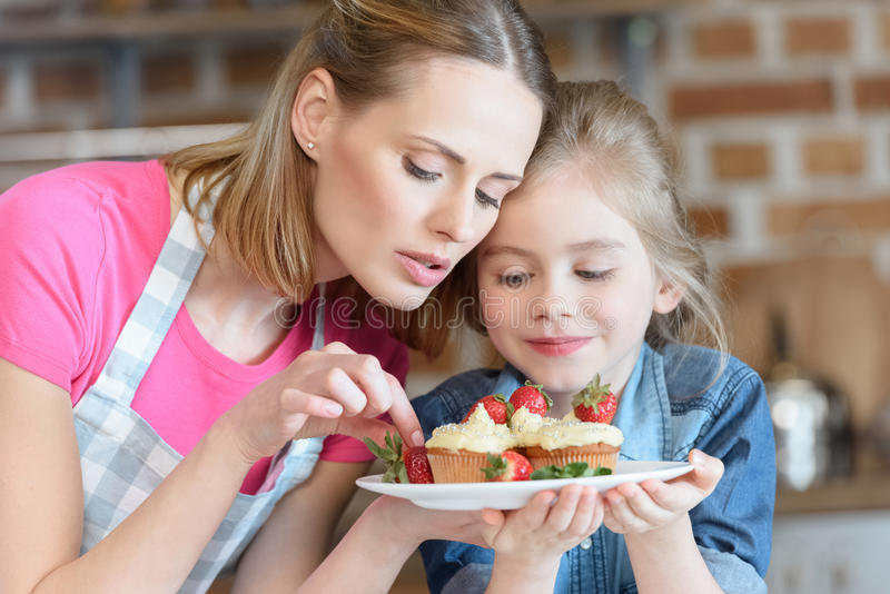 Mother and daughter holding homemade cupcakes with strawberries. Portrait of mother and daughter holding homemade cupcakes with strawberries royalty free stock image
