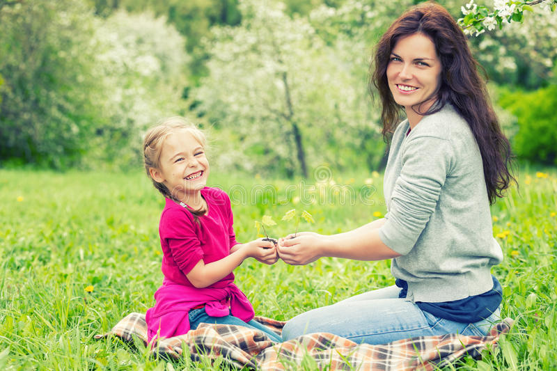 Mother and daughter holding little green plant in hands stock photo