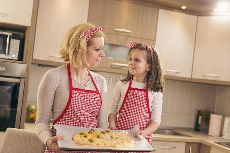 Mother and daughter holding pizza ready for baking royalty free stock images