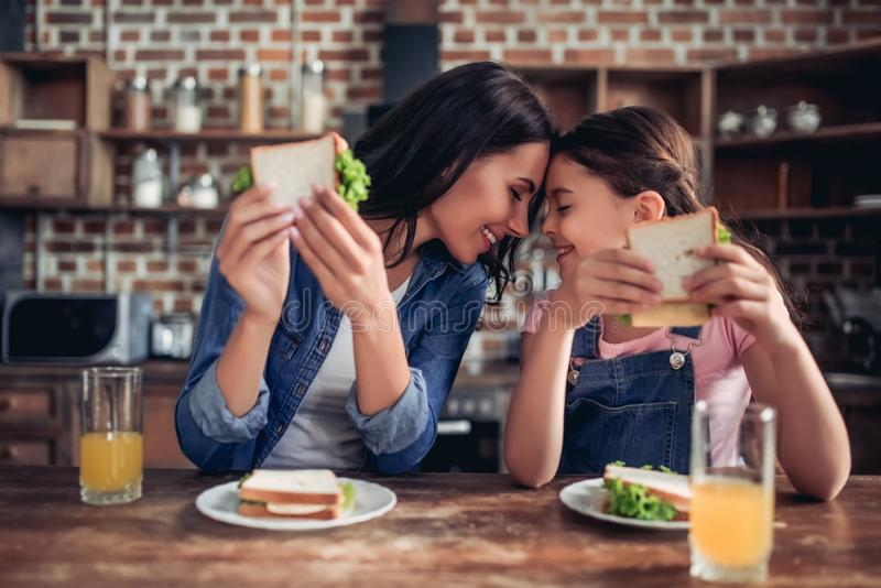 Mother and daughter holding sandwiches. Caucasian mother and daughter holding sandwiches and looking at each other in the kitchen royalty free stock photography