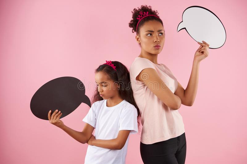Mother and daughter are holding speech bubbles. stock image