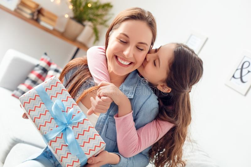 Mother and daughter at home mother`s day sitting daughter hugging mom holding present kissing royalty free stock images