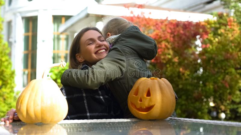 Mother and daughter hugging on backyard, happy childhood, celebrating Halloween. Stock photo stock image