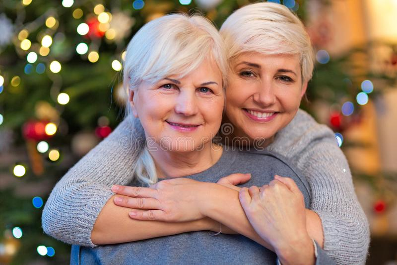 Mother and daughter hugging by Christmas tree royalty free stock photo