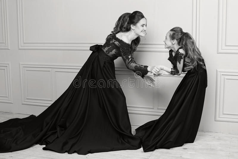 Mother and daughter hugging and looking at the camera. Happy loving family. Mother and daughter in beautiful long luxury blue dres royalty free stock photography
