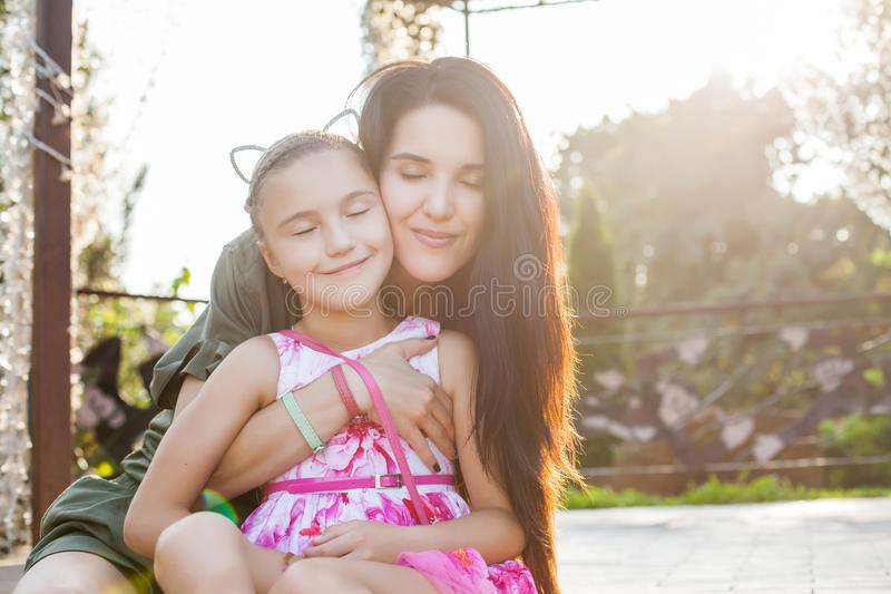 Mother and daughter hugging and smiling with closen eyes. Attractive mother and daughter hugging with closen eyes and smiling. Concept of happy loving family stock images