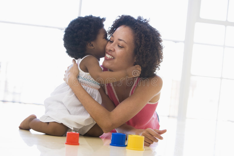 Mother and daughter indoors kissing royalty free stock photos