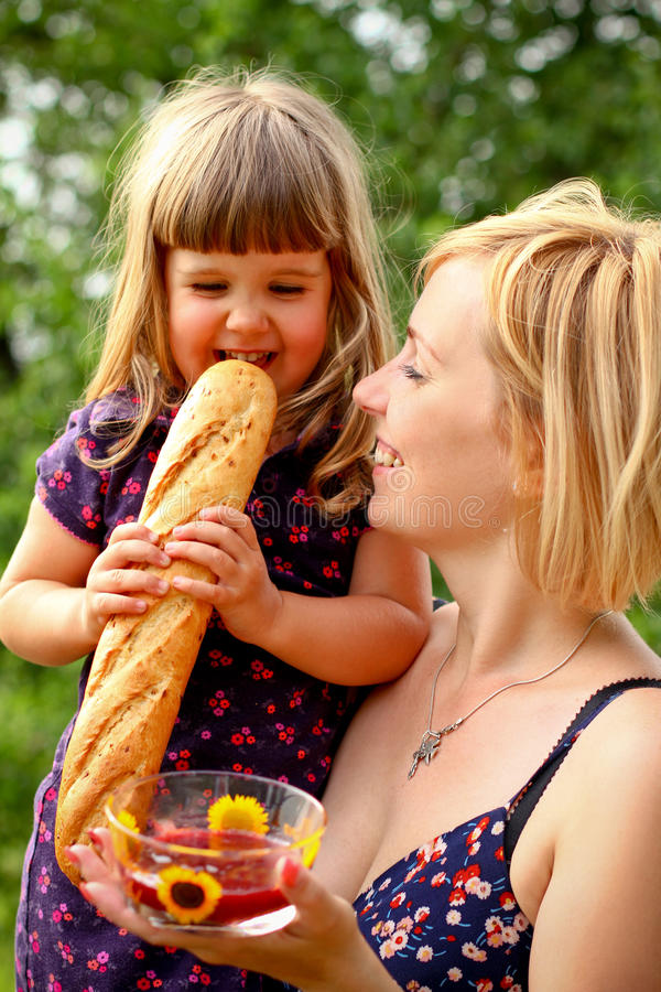 Mother and daughter with jam and bread outdoors royalty free stock photos