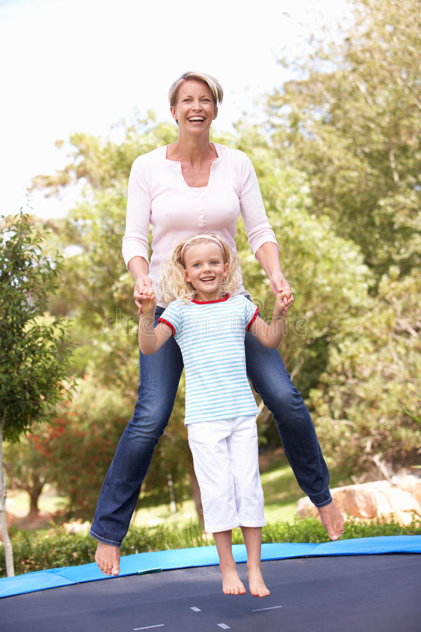 Download Mother And Daughter Jumping On Trampoline In Garde Stock Image - Image: 15083171