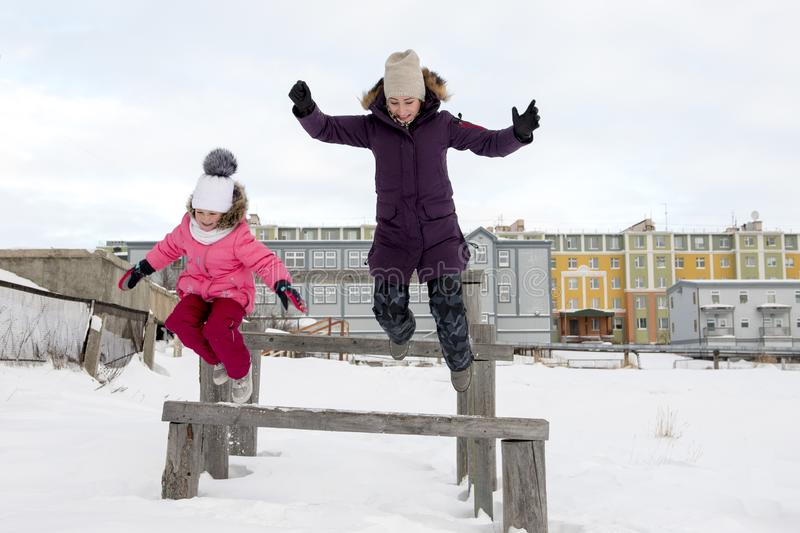 Mother and daughter jumping in the snow royalty free stock images