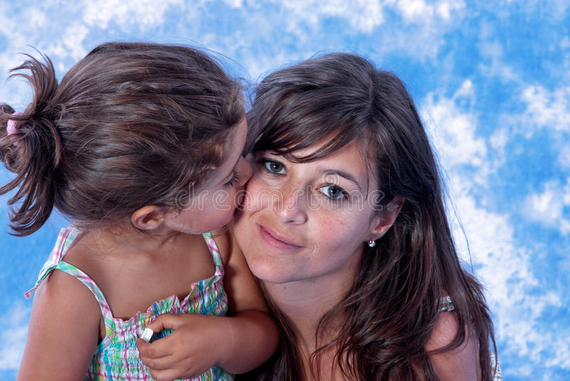 Mother and daughter kiss stock photos