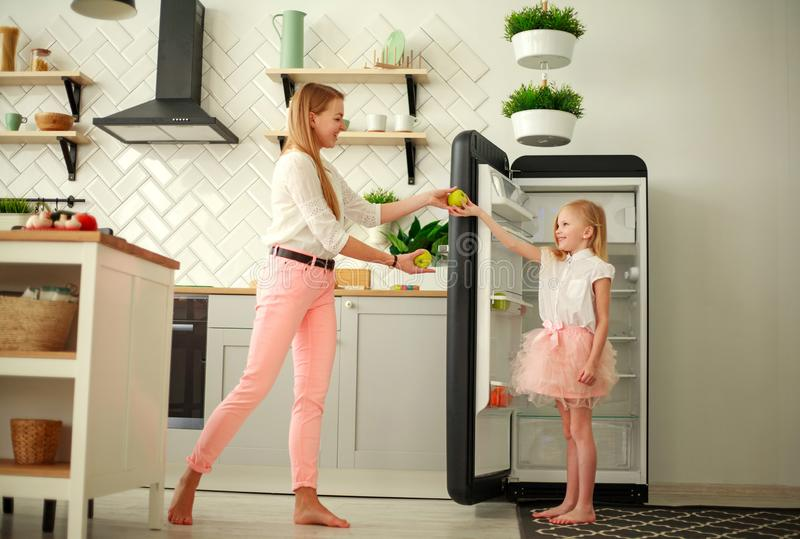 Mother and daughter in kitchen put fruits and apples in refrigerator, home family healthy lifestyle royalty free stock photos