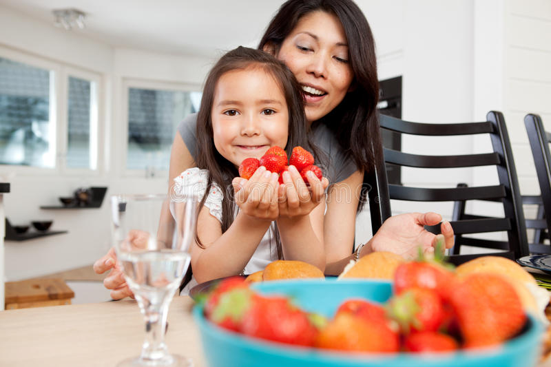 Mother and Daughter in Kitchen with Strawberries stock image