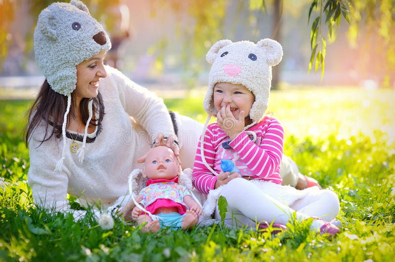 Mother and daughter in knit hats bears in the park stock photo
