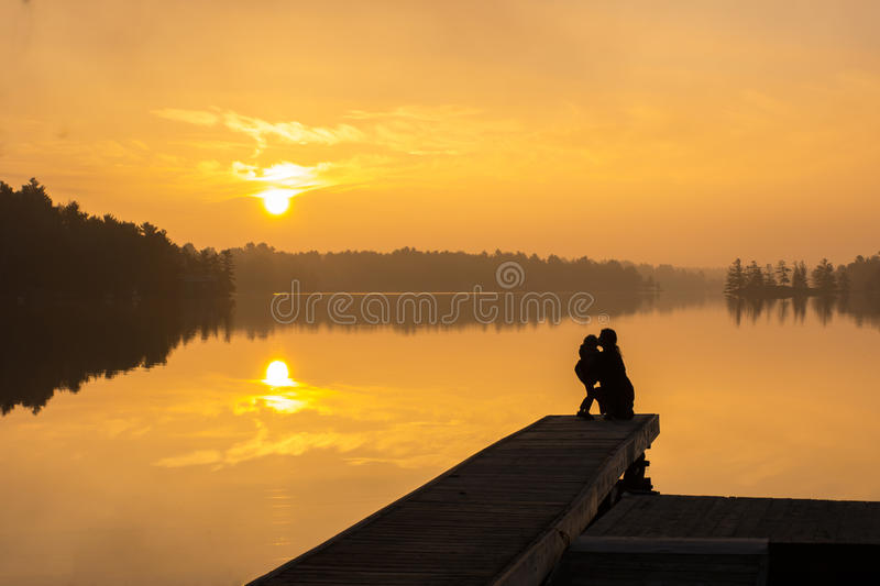 Mother & Daughter Lake Sunrise Kiss. A Mother and daughter kiss while enjoying a lake sunrise together stock photos