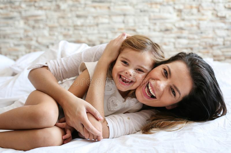 Mother and daughter laying in bed. stock images