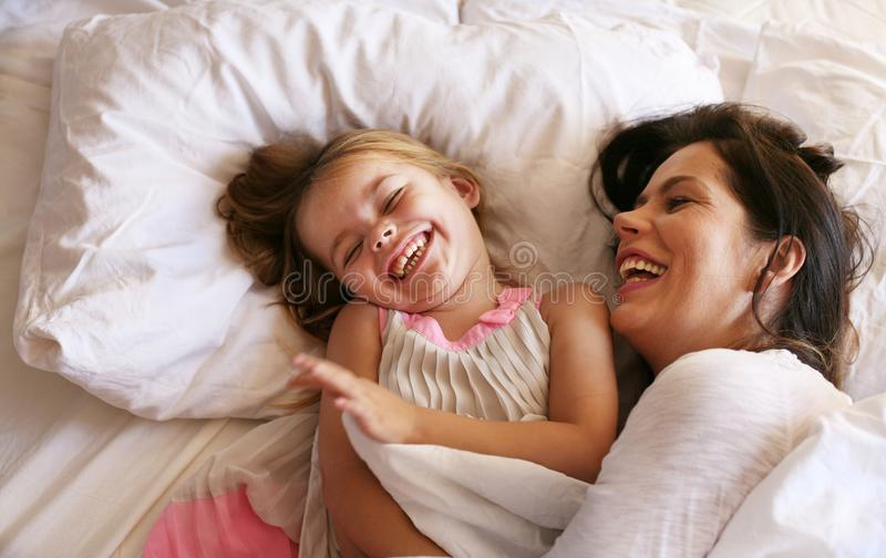 Mother and daughter laying in bed. stock photos