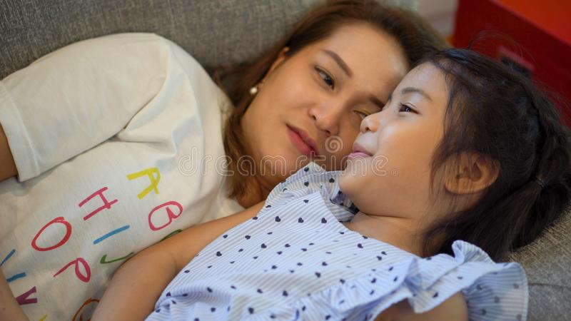 Mother and daughter laying on sofa and talking together. Happy loving family.  child girl  playing and hugging Mom on bed in royalty free stock image