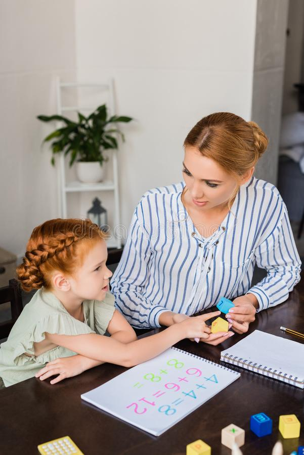 Mother and daughter learning math at home stock images