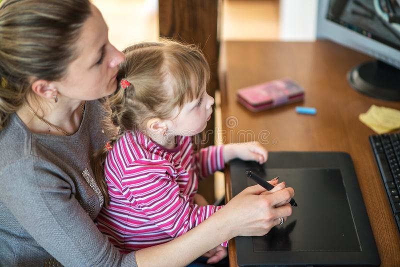 Mother and daughter learning painting with pen tablets, child development, IT technology and tools, design and graphics stock images