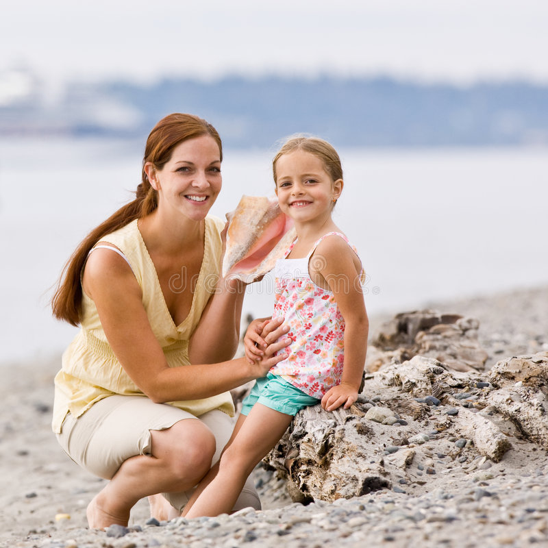 Mother and daughter listening to seashell at beach