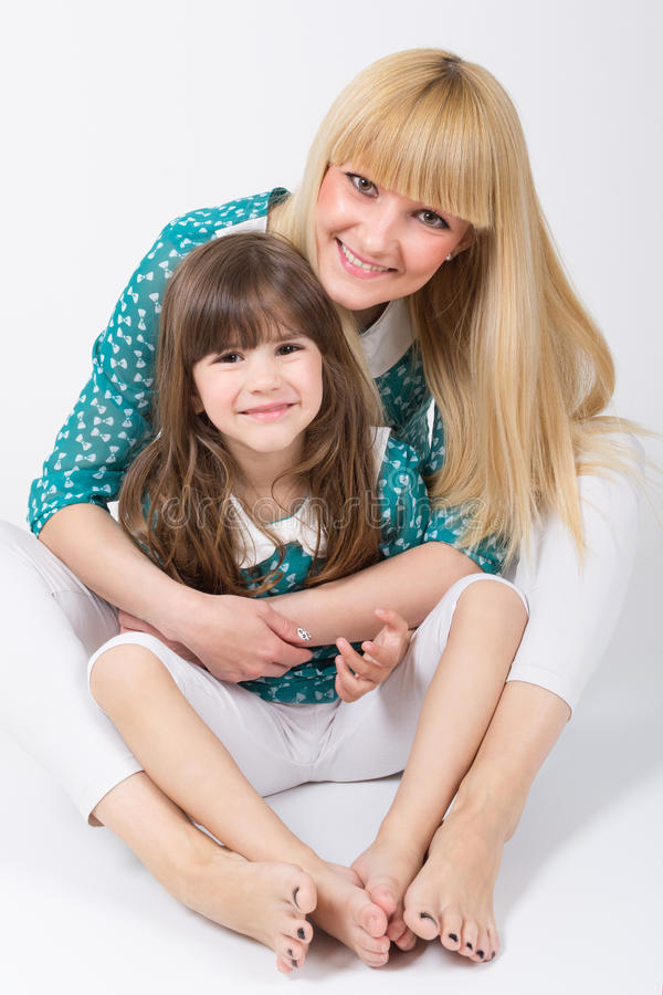 Mother and daughter with long hair with bangs huging and smiling. Cute Caucasian blonde mother and brunet daughter with long similar haircuts with bangs hugging royalty free stock photos