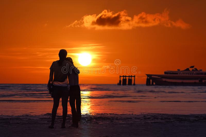 Mother and daughter look at sunset on the beach royalty free stock photos