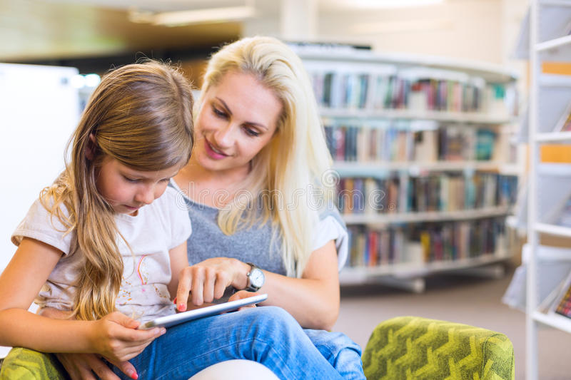 Mother with daughter look at their touchpad tablet device togeth stock image