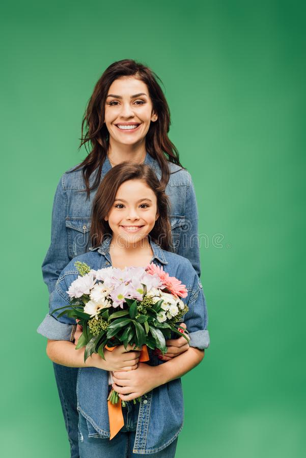 Mother and daughter looking at camera and holding flower bouquet isolated royalty free stock images