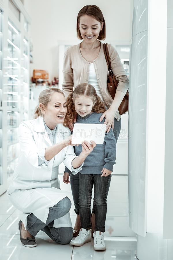 Mother and daughter looking at druggist s tablet interestedly stock photo