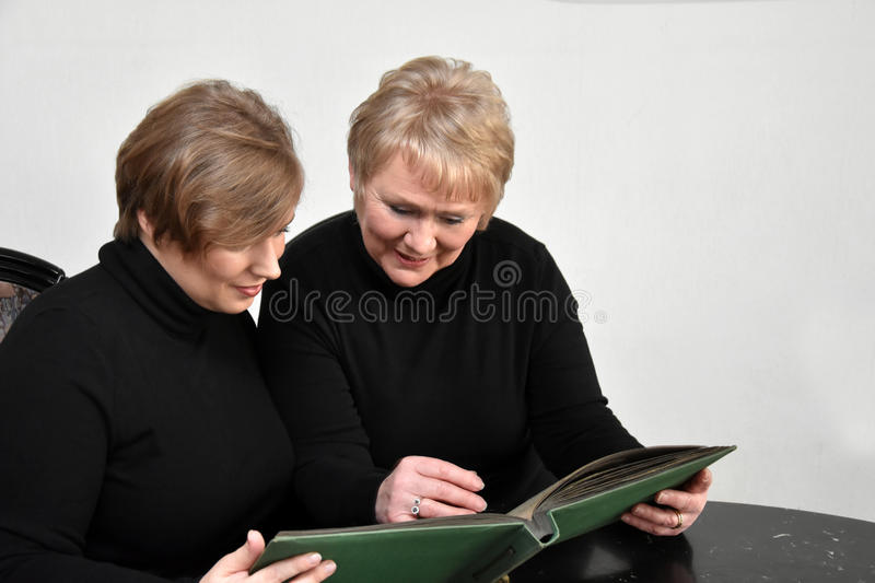 Mother and daughter looking at photo album. Mother and daughter having fun while looking at old pictures in a photo album stock images