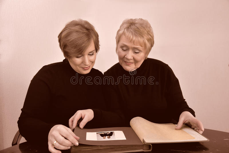 Mother and daughter looking at photo album. Mother and daughter having fun while looking at old pictures in a photo album royalty free stock photo