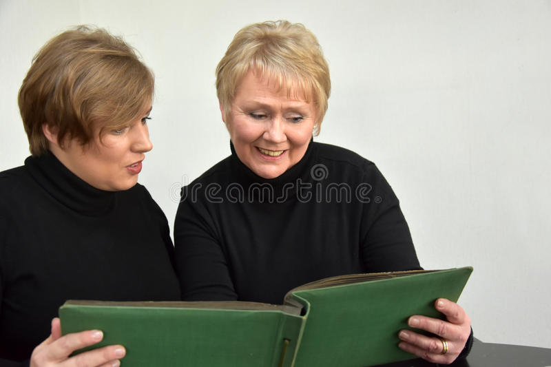 Mother and daughter looking at photo album. Mother and daughter having fun while looking at old pictures in a photo album royalty free stock photos